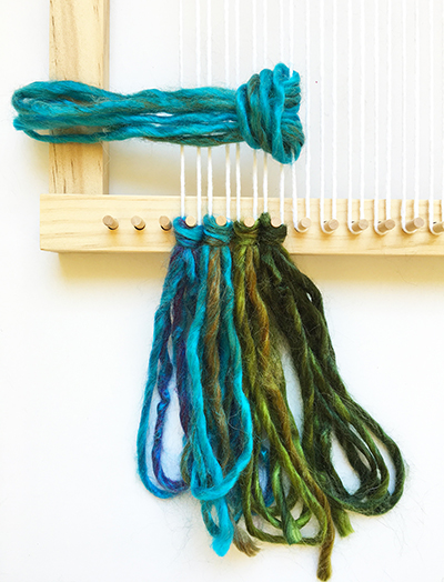 Attaching tassels to a mixed-media weaving