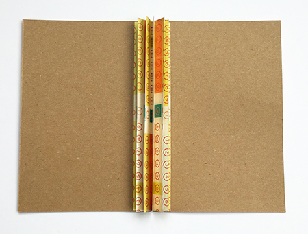 Binding bar glued to the covers of an envelope journal